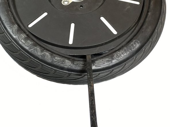Use the persuasion bar to begin pulling the rubber back over the rim of the tire. When you pull the rubber back over the tire, push the persuasion bar away from you and towards the other side of the tire to put the rubber of the tire back onto the rim.