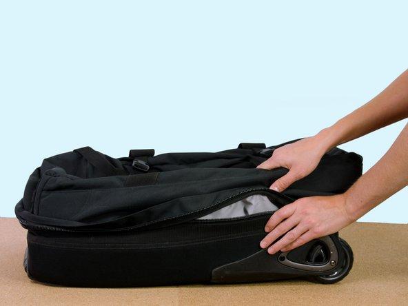 Das Hauptfach der Tasche öffnen, bis es flach auf dem Tisch liegt.