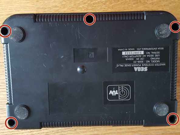 Flip the console on it's back and unscrew the 5 screws marked on this photo.
