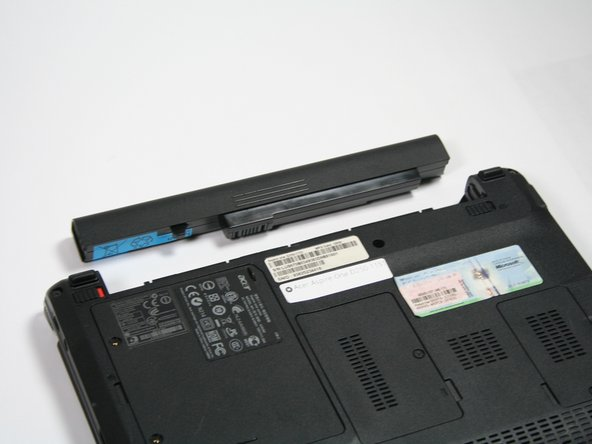 Push forward on the battery lines while holding the tab on the right.