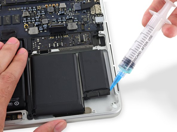 Apply a small amount of adhesive remover (approximately 1 ml) evenly under the edge of the rightmost battery cell.