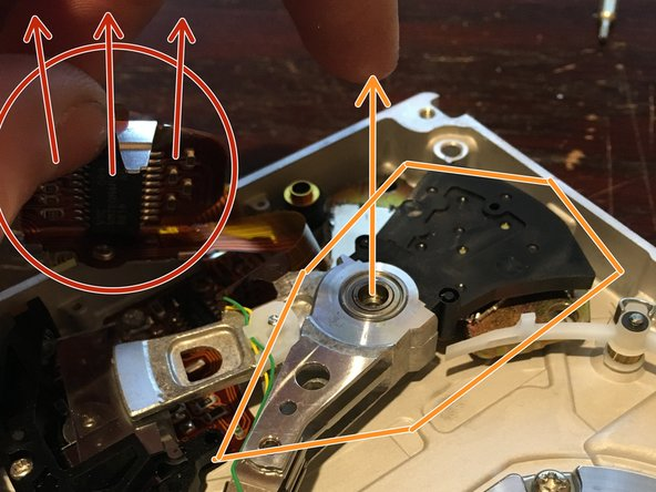 "Now, you can pull on the metal tab (circled in  red), and pull off both the read/write head and some of the ribbon cables. Lift straight up to detach the read/write head (""circled"" in orange - follow the orange arrows). Now, you can remove the bottom neodymium magnet. Pull it straight up, and don't put it near the other magnet!"