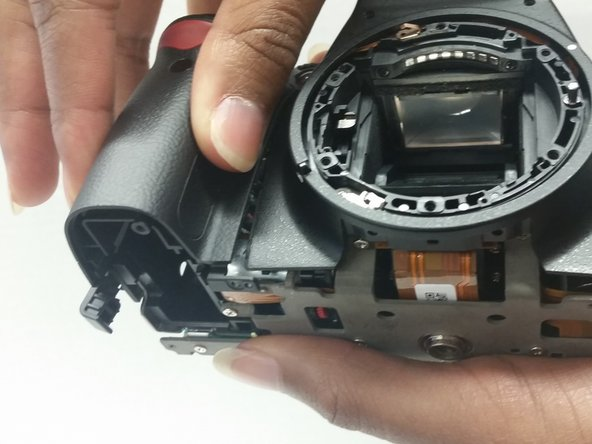 Image 2/2: Lift and remove the grip and the front panel of the camera.