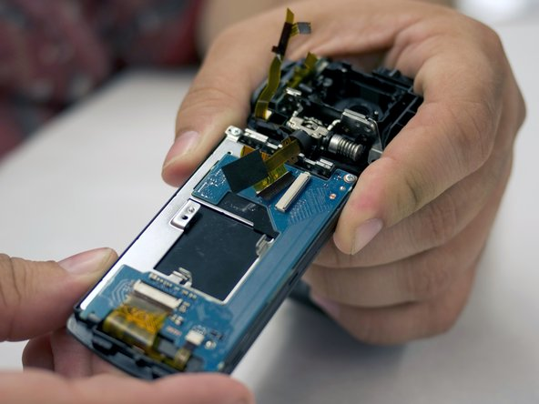 With tweezers, remove the ribbon cable that is connecting the LCD screen board to the motherboard.