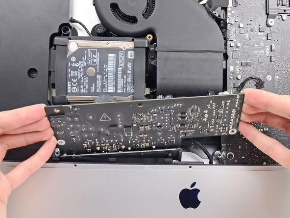 Image 2/3: '''Do not''' try to completely remove the power supply from the iMac yet—it is still connected to the logic board.