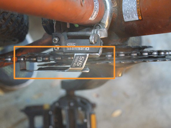 The chain should be roughly centered in the derailleur, so that no extra friction is caused, and that the chain is not unintentionally pushed off the sprocket.