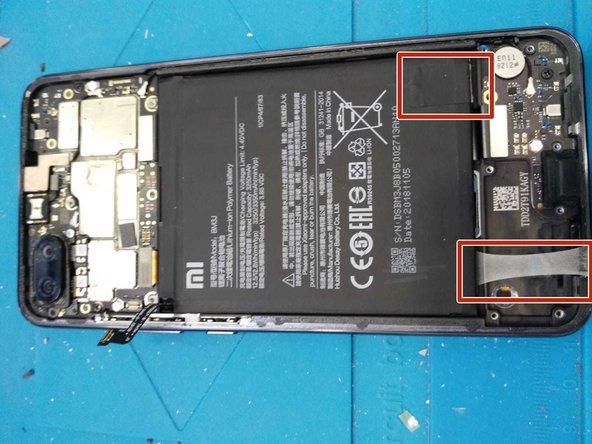 tira con cuidado a los dos adhesivos que pegan a la batería junto al marco intermedio.
