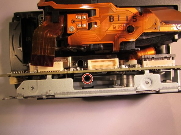 Remove the black 4 mm screw underneath the motherboard.