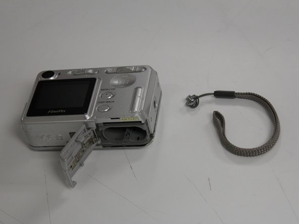 Image 3/3: Once the two halves of the case have begun to come apart, pull the wrist strap away from the front of the camera to remove it.