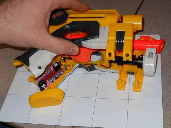 Image 2/3: Lift the side of the blaster off exposing its internal parts.