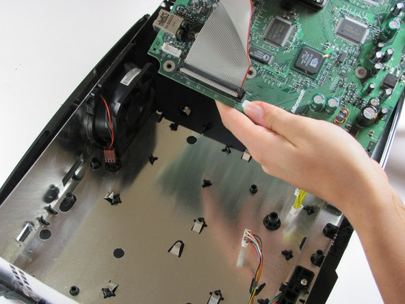 Remove the motherboard from the Xbox. As long as all of the screws are out and the fan is disconnected, it will lift out easily.
