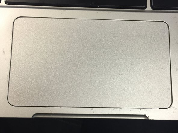 Finish applying the track pad cover and firmly press it to the track pad board.