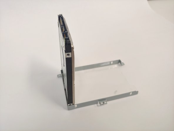 Use your fingers and gently lift the hard drive from the case it was screwed into.