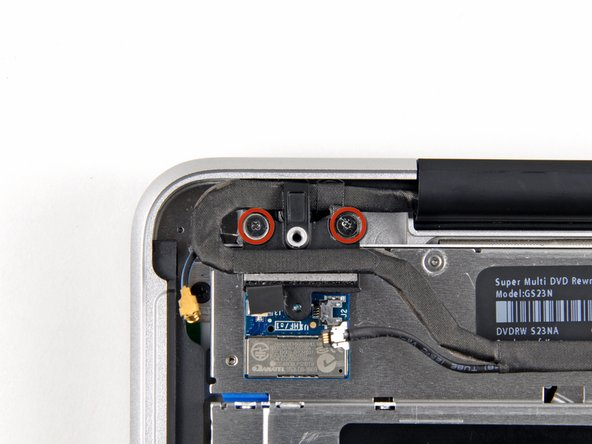 Image 1/2: Remove the two 8 mm Phillips screws securing the Bluetooth/camera cable retainer to the upper case.