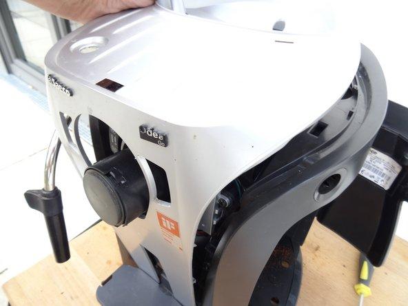 Das große silberfarbene Formteil über der Ober- und Vorderseit ist jetzt nur noch mit Rasten befestigt, die allerdings ziemlich festsitzen können. Benutze zum Loshebeln nur Werkzeuge aus Kunstoff.