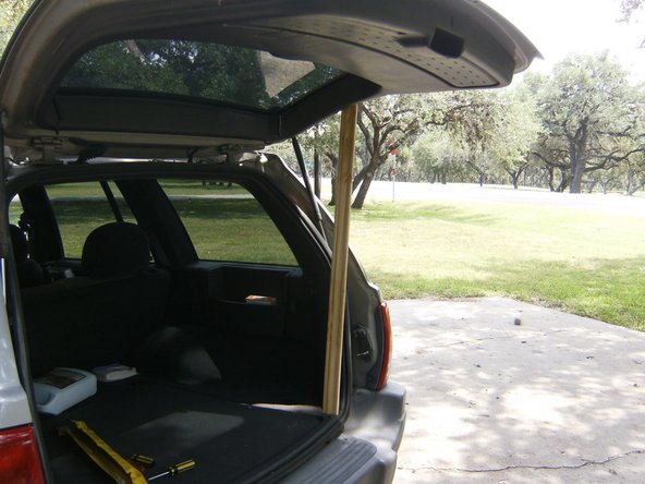 Open the tail gate and either prop it up or use an assistant to hold it.