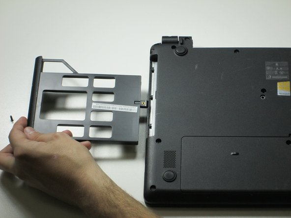 Slide out the plastic insert located on the left side, and remove, before returning the laptop to the face-up position.