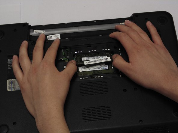 Place both thumbs on the latches and push outward. The RAM card will pop up.