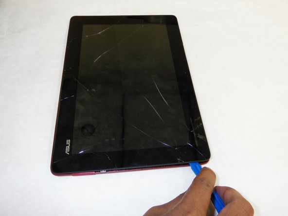Use plastic opening tool to pry screen up and remove the main tablet body  from outer rim casing.