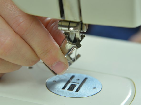 Image 2/3: Take the foot at an angle and slide the hole in the top of the presser foot onto the peg on the sewing machine.