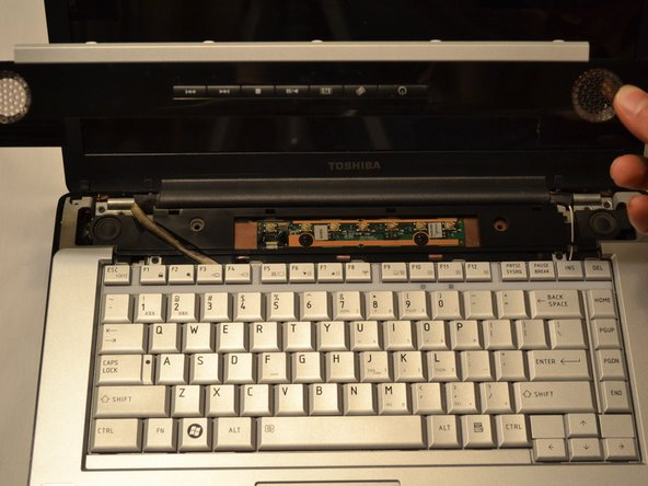 Flip the laptop over, and push the bezel towards the lcd while lifting up, this might require some force.