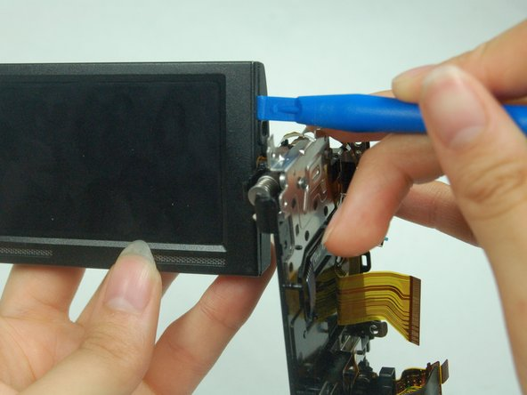 Use the plastic opener tool to loosen the casing between the screen's front and back.