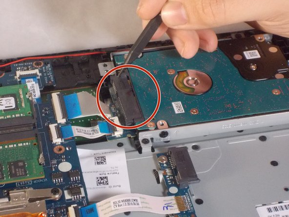 Using a black nylon spudger, disconnect the black connector that attaches the hard drive to the motherboard