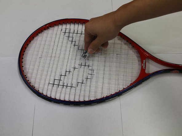 Use your cutting tool to cut the racket strings.