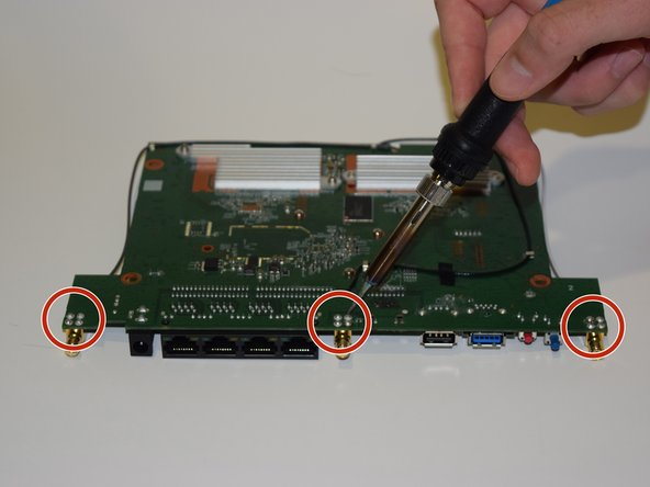 Locate the four solder points on each port and melt them  using a soldering iron.