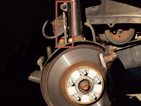 The sway bar link is located behind the brake shield, connecting the sway bar and suspension.