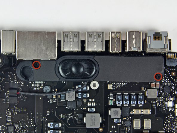 Remove the two 5 mm Phillips screws securing the left speaker to the logic board assembly.