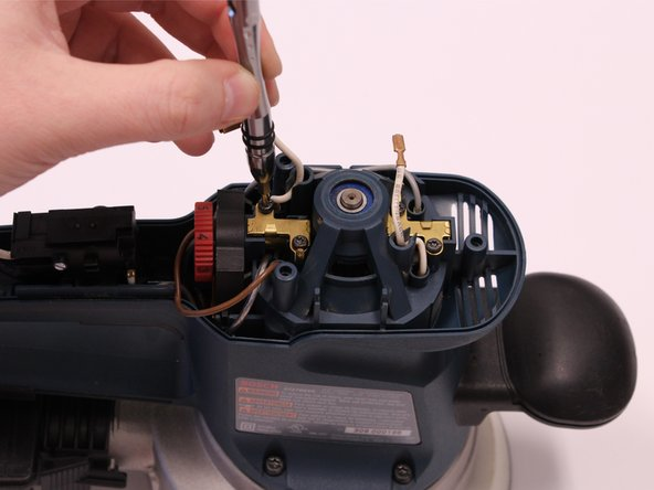 After the screws are removed, both motor brushes can be lifted out of their position by hand.