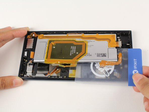Use the plastic card to push under the battery to further remove the adhesive.
