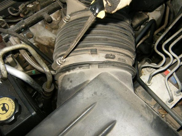 Loosen the clamps from the air intake duct to remove the air cleaner cover from the engine.
