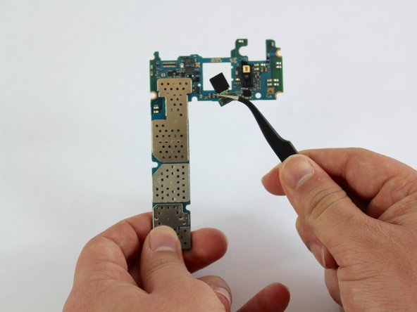 Use the tweezers to remove the front camera from the motherboard.