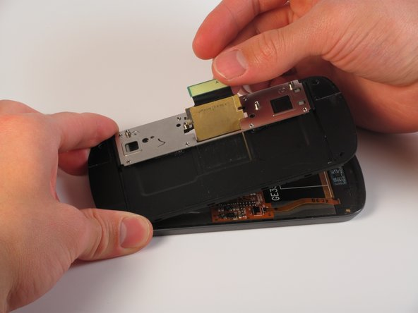 Lift the flex cable and position it so the part containing the metal plate can come free.