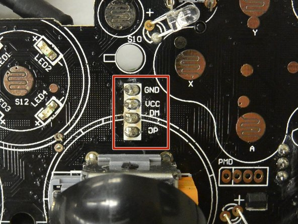 The cable connects to the logic board with a white connector. Above the right joystick, there are four solder pins labeled GND, VCC, DM, and DP.