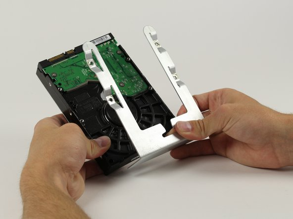 Image 3/3: Using a Phillips head screw driver remove the four screws and separate the metal sled from the Hard Drive