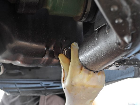 Place the oil drain plug back over its hole and turn it clockwise by hand as far as possible.