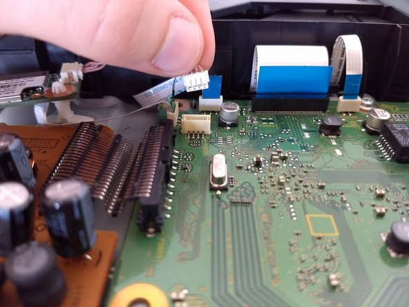 Locate reddish brown cable. Detach from green circuit board by pulling upward.