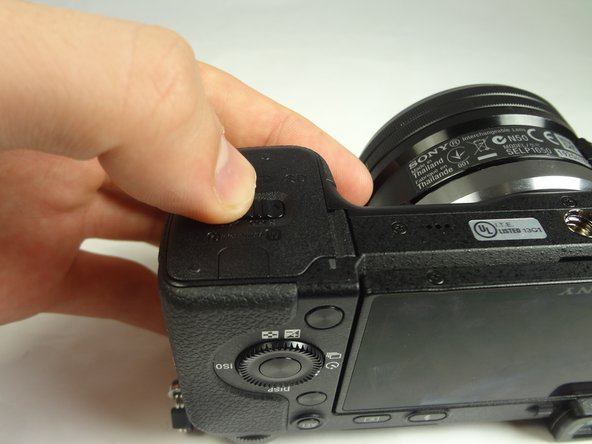 Image 1/1: With the lens facing outward, locate the battery compartment - indicated by a grooved latch.