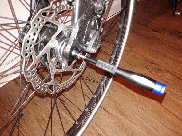 Insert the front wheel into the fork and tighten the axle bolt with the 4mm Allen key / Allen key.