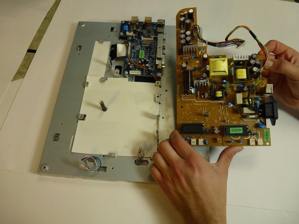 Lift the brown power supply board off of the frame and set it aside.