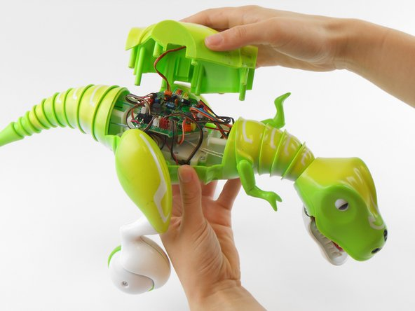Image 2/2: Be gentle while removing the back cover. The back cover of the Zoomer Dino Boomer is still connected to the electronic system by a wire.