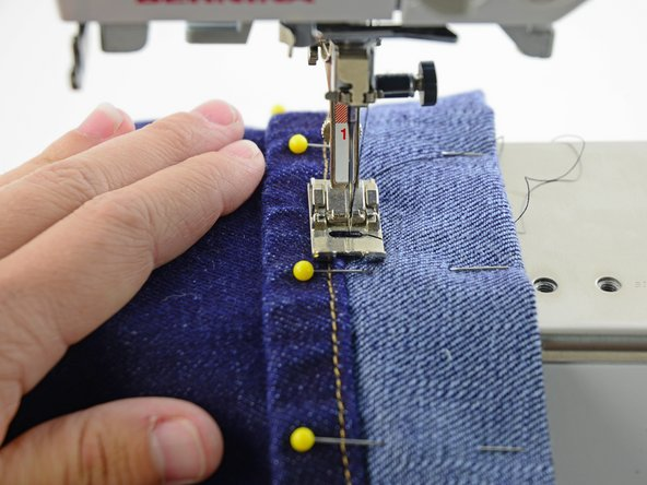 Lower the presser foot and take a few stitches, keep the line of stitches right at the edge of the hem.
