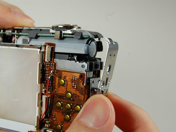 Image 2/2: Slowly pull the side casing so it becomes dislocated from the top of the camera frame.