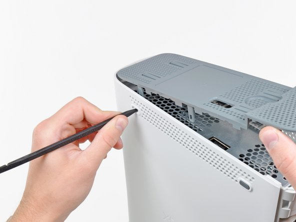 Use the tip of your spudger to release the clip on the top vent nearest the back of the Xbox.