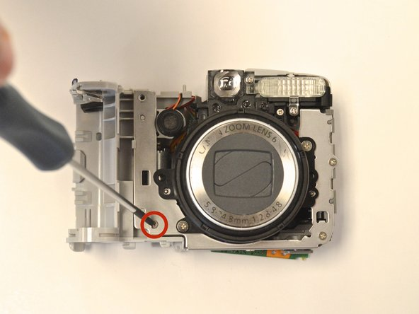 With the lens facing up, remove the 3 mm phillips head screw that attaches the bottom of the battery housing unit to the lens.