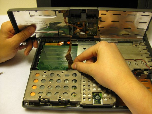 Remove the front plastic panel of the laptop by carefully lifting it up.