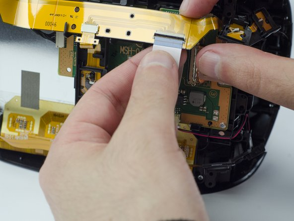 Carefully pull the end of the white ribbon connector from its slot.